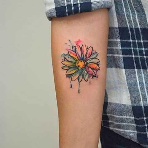 Foto a cores de tatuagem de camomila no antebraço da menina