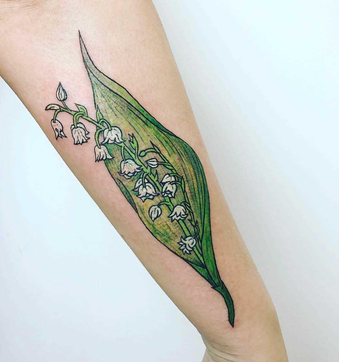 Foto a cores de tatuagem, lírio do vale no antebraço da menina