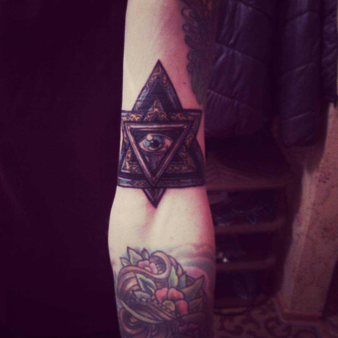 Foto a cores de tatuagem piscar de olhos que tudo vê na mão de um cara