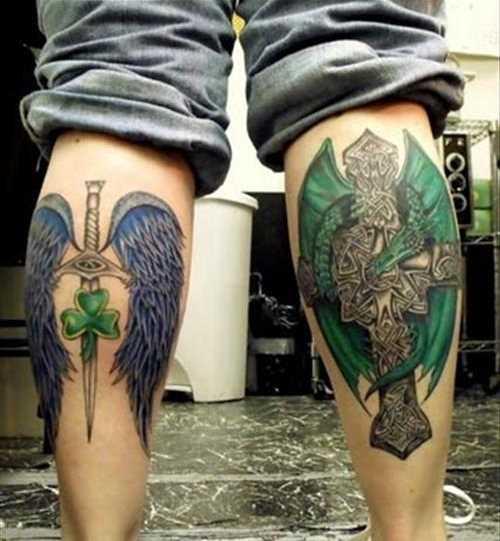 Foto a cores de tatuagens de asas e uma cruz em estilo gótico sobre a perna de um cara