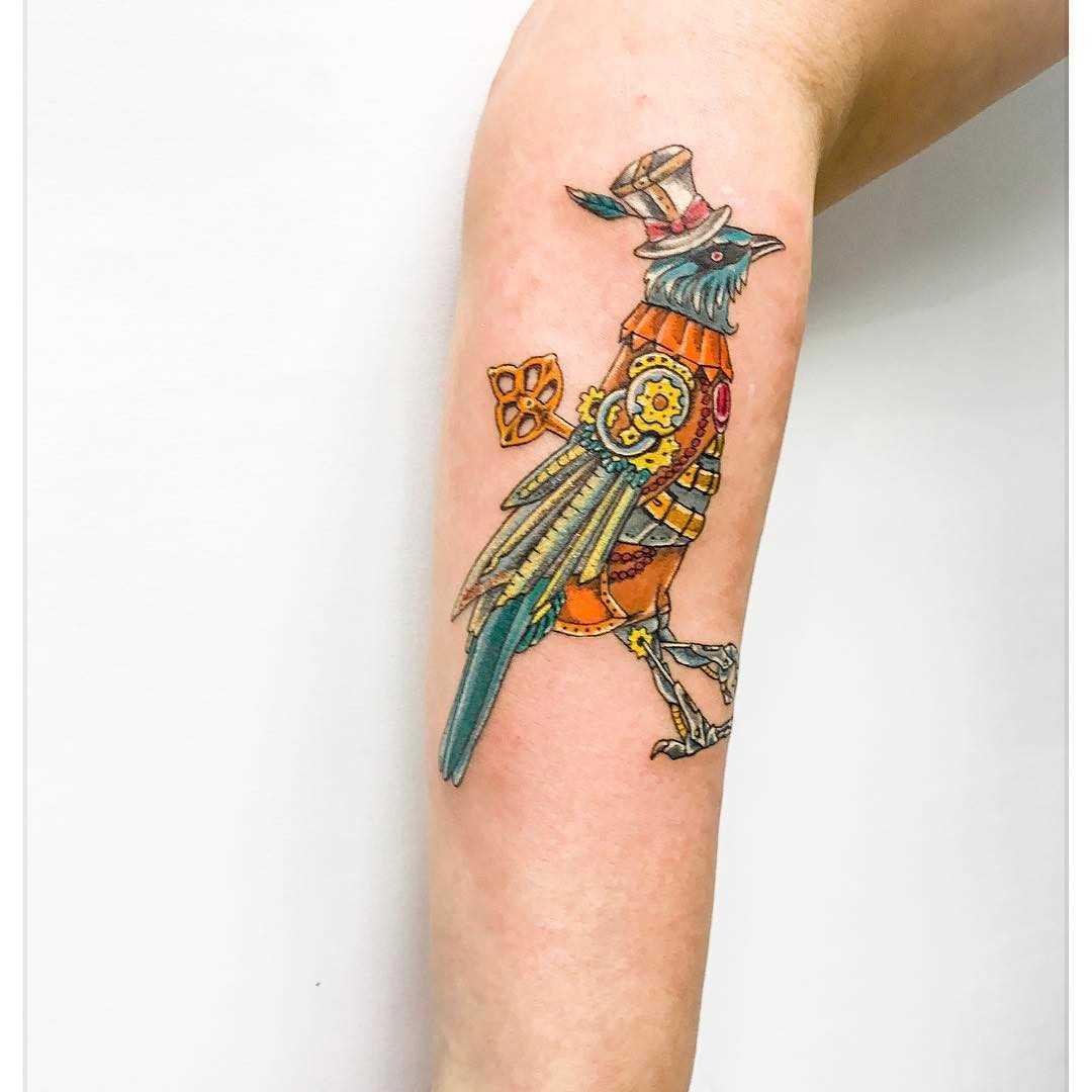 Foto a cores de uma tatuagem de um pássaro no estilo steampunk no antebraço cara