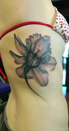 Foto da bela tatuagem de narcisos sobre as costelas menina