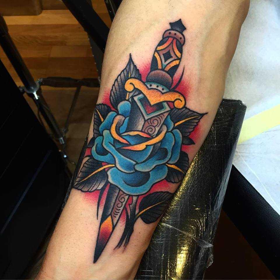 Foto da tatuagem azul rosa com um punhal no antebraço cara