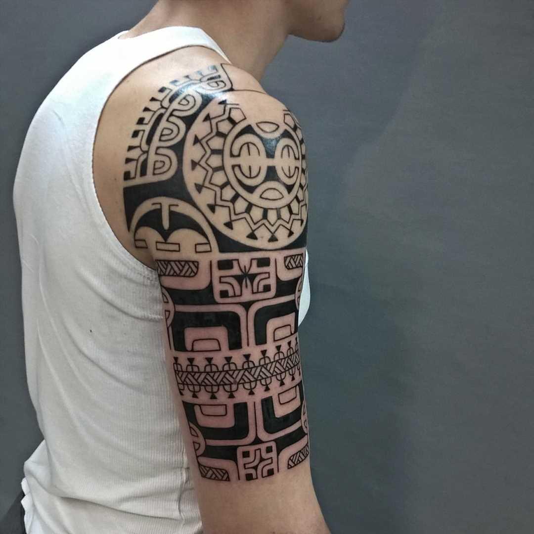 Foto da tatuagem em estilo polinésia no ombro do cara
