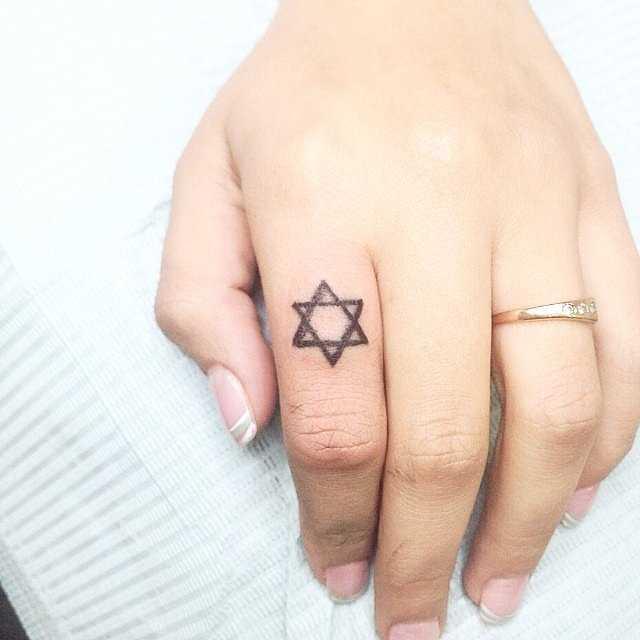 Foto de uma pequena tatuagem da estrela de david em hebraico moderno no dedo de uma menina