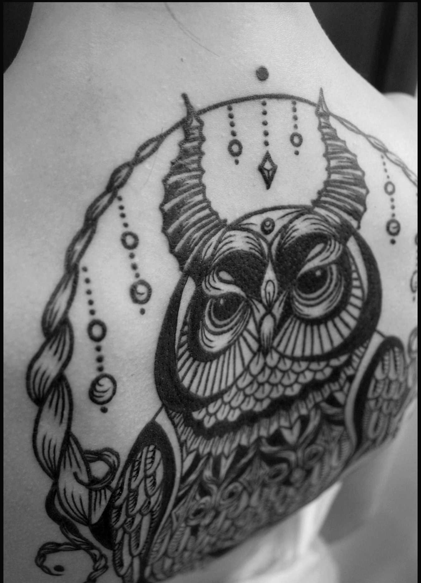 Foto de uma tatuagem de coruja em um estilo de gráfico na parte de trás da menina