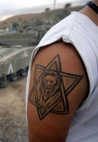 Foto de uma tatuagem de estrela de davi com o leão no bairro judeu de estilo no ombro de homens