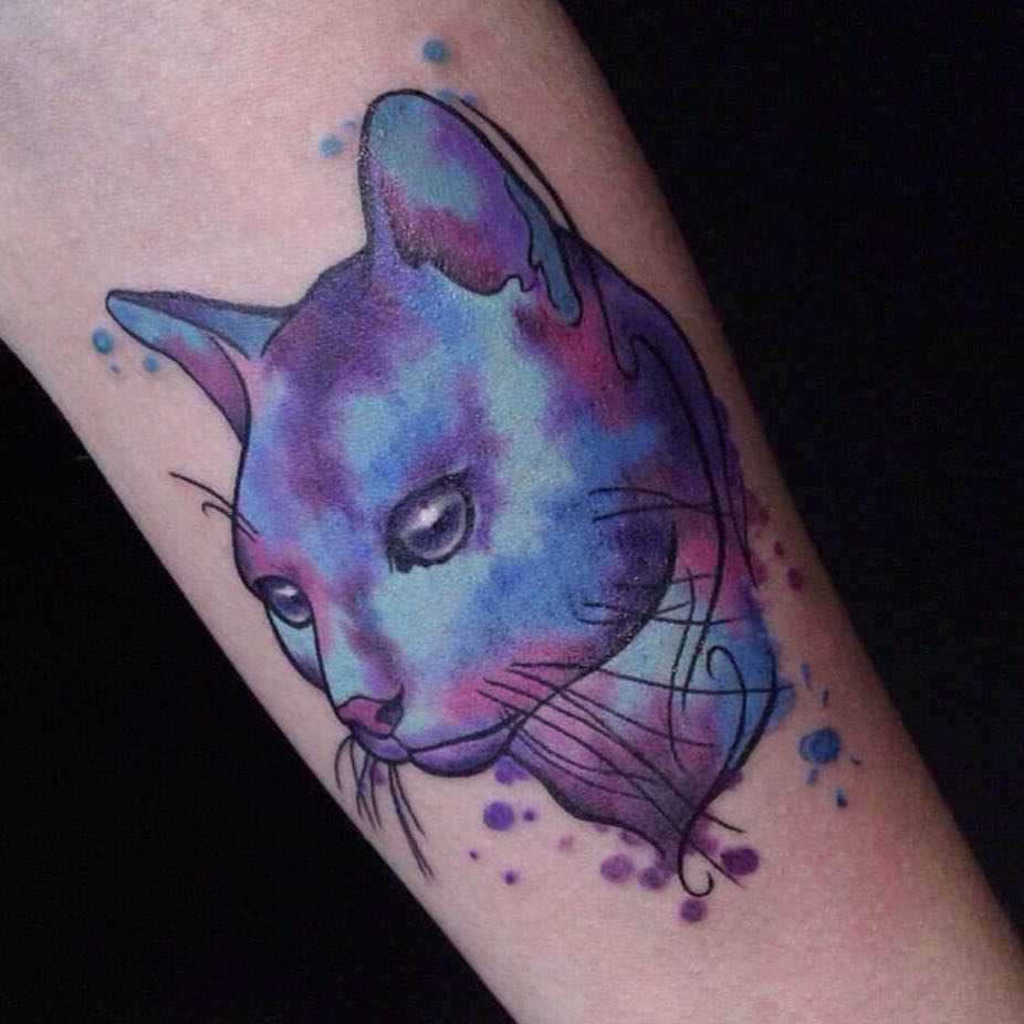 Foto de uma tatuagem de gato no estilo aquarela no antebraço da menina