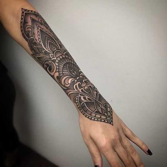Foto de uma tatuagem em estilo indiano no antebraço da menina