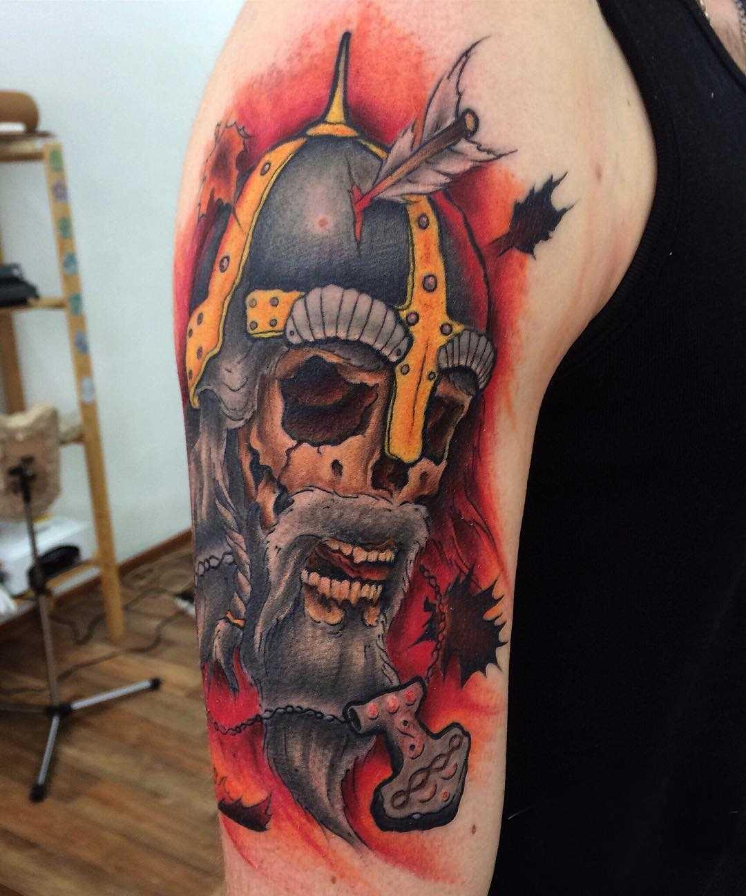 Foto íngreme da tatuagem de caveira no estilo newschool no ombro do cara