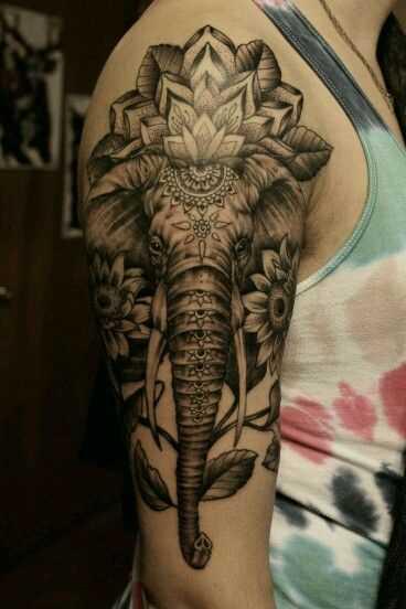 Foto íngreme da tatuagem de um elefante em estilo indiano no ombro do cara