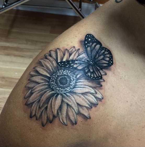 Fotos de tatuagem de camomila com uma borboleta no ombro da menina