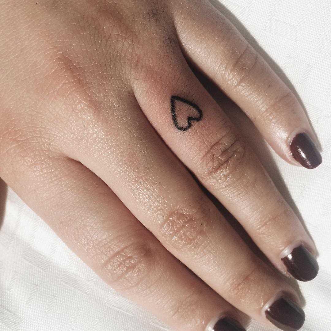 Fotos de tatuagem de coração no estilo handpoke no dedo de uma menina
