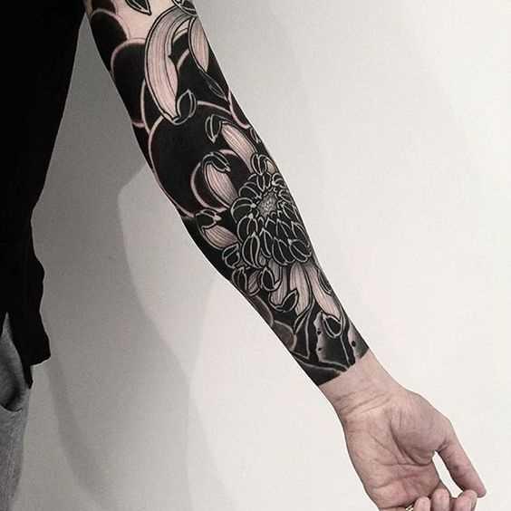 Fotos de tatuagem de flores no estilo de blackwork na manga cara