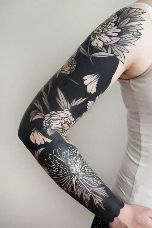 Fotos de tatuagem de flores no estilo de blackwork na manga da menina