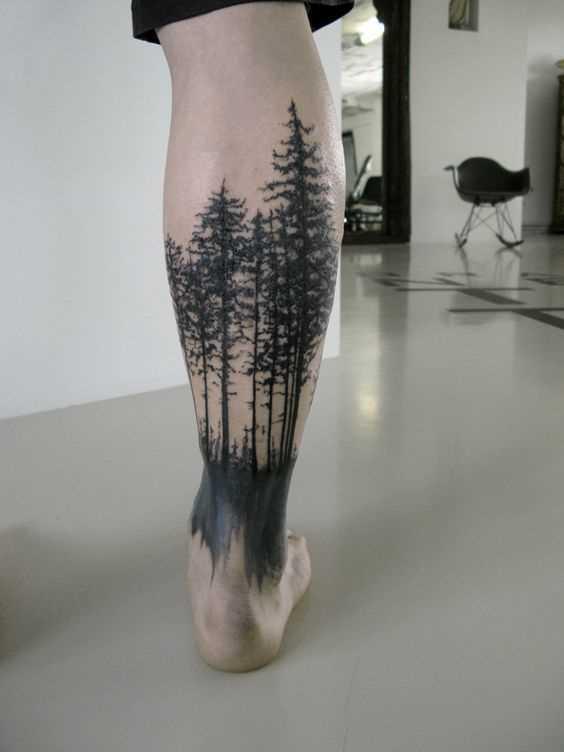 Fotos de tatuagem de floresta no estilo de blackwork sobre a perna de um cara