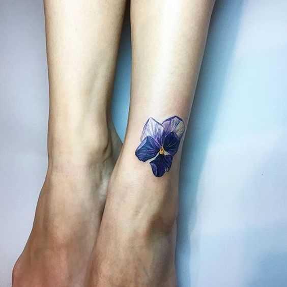 Fotos de tatuagem de violeta sobre a perna da menina