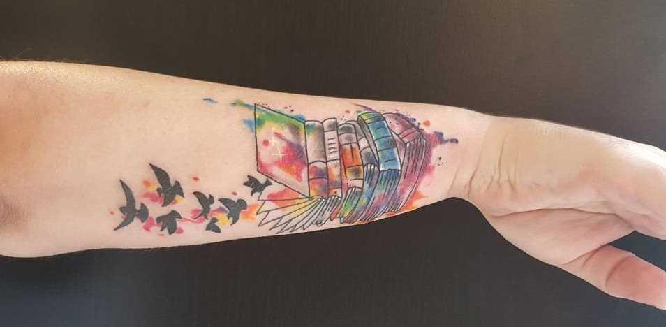Imagem da cor de livros com os pássaros no antebraço da menina