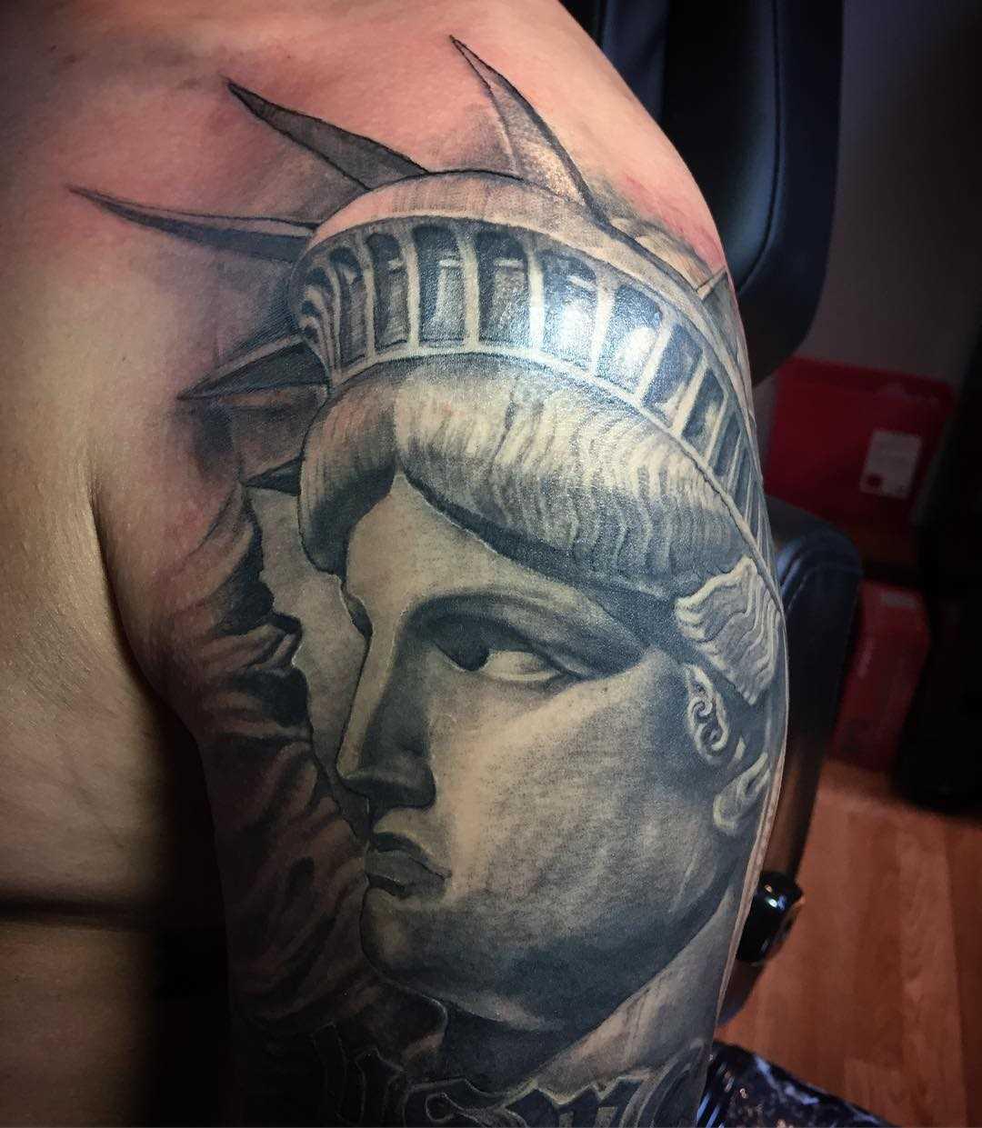 Imagem da estátua da liberdade no ombro de homens