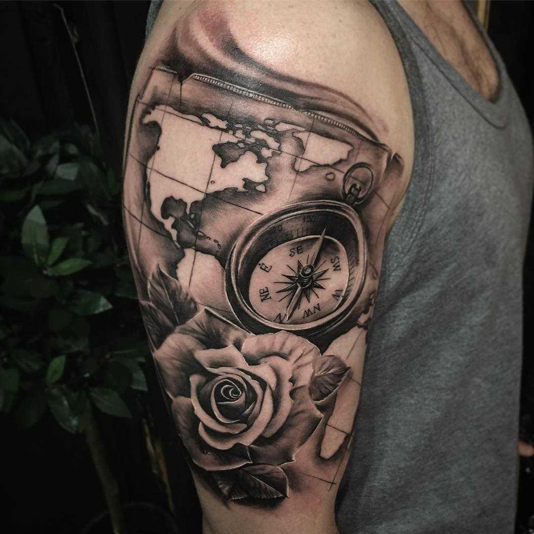 Íngreme desenho de uma bússola, com uma rosa e um cartão de no ombro do cara