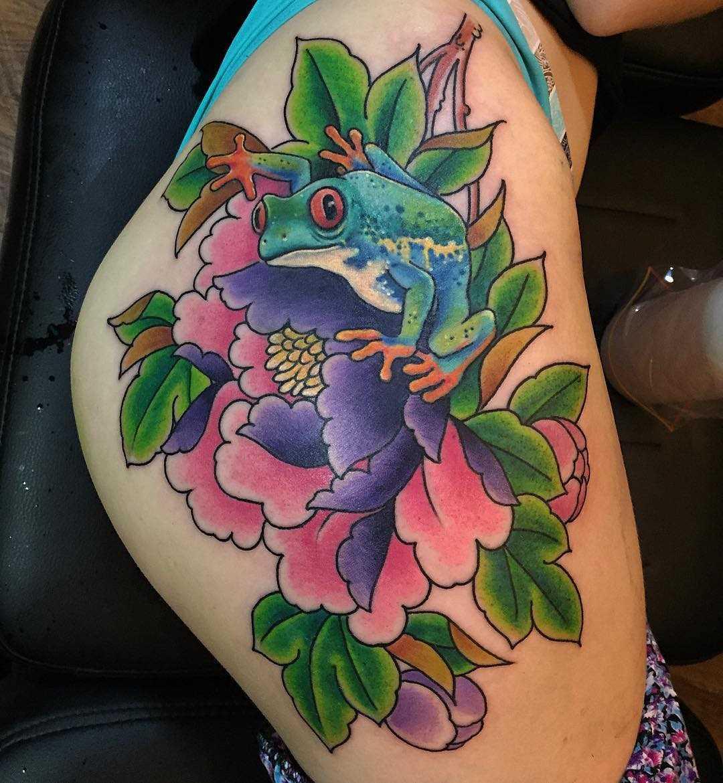 Legal a tatuagem de um sapo com flores no quadril da menina