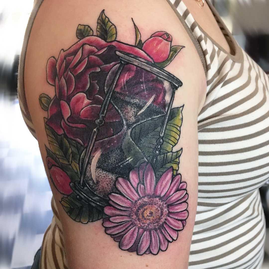 Linda tatuagem de ampulheta com flores no ombro da menina