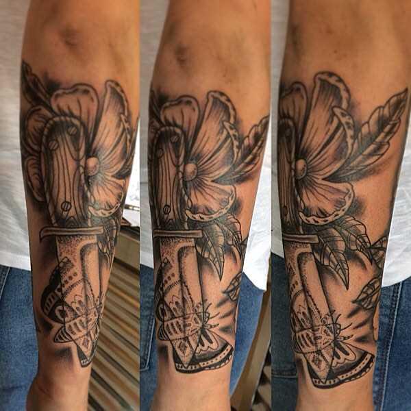 O desenho da faca com a flor no antebraço cara
