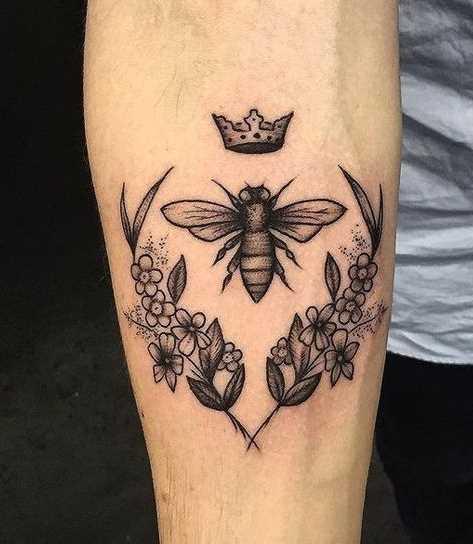 O desenho de uma abelha com flores no antebraço homens
