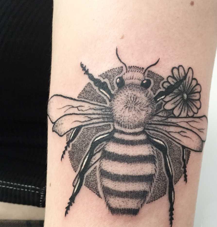 O desenho de uma abelha na mão de um cara