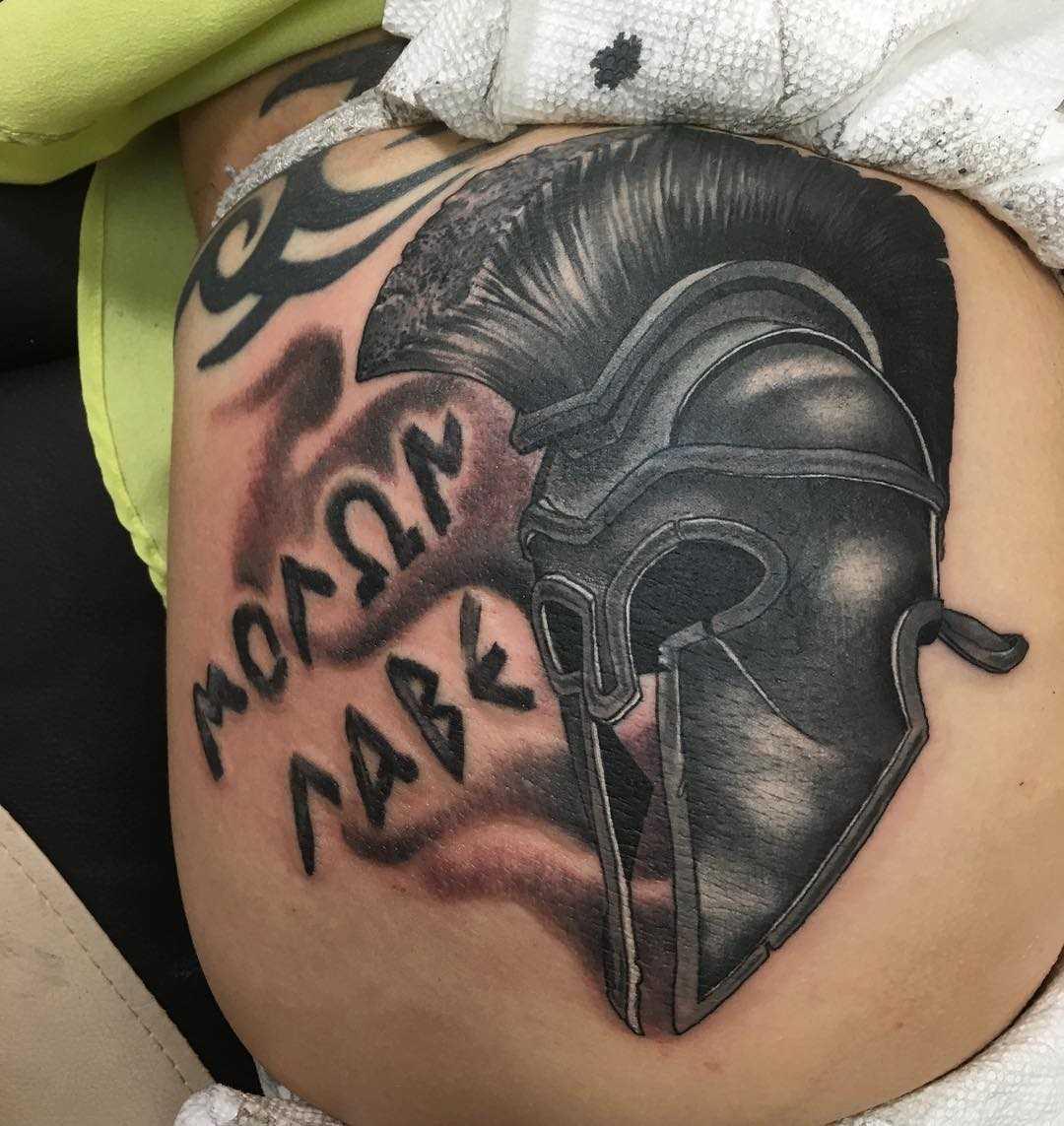 O desenho do capacete espartano com a inscrição na coxa da menina