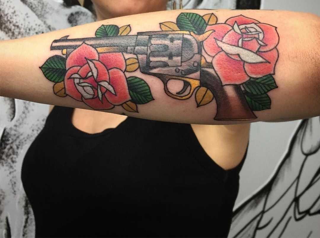 O desenho do revólver com rosas no antebraço da menina