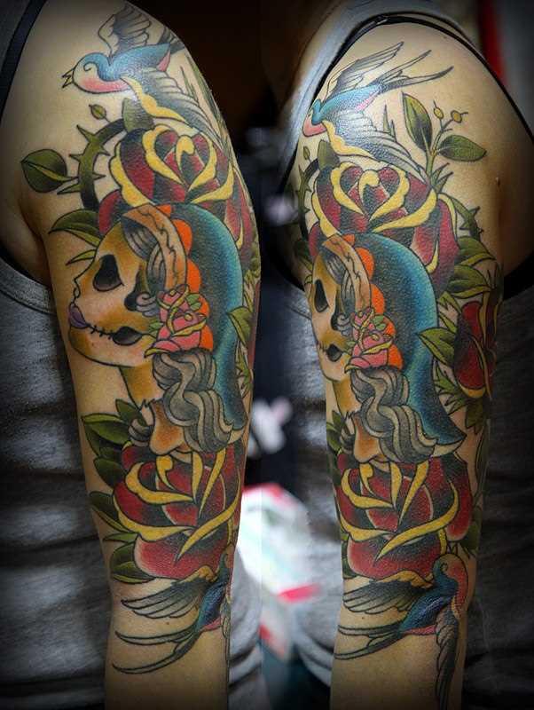 Oldschool tatuagem que tem no braço da menina - uma andorinha e um mexicano crânio