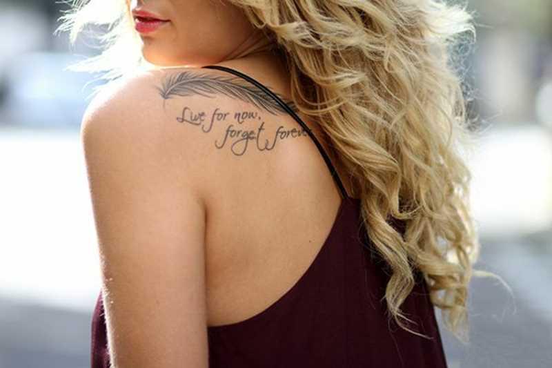 Preto-e-branco de uma tatuagem de uma menina no ombro em forma de caneta e inscrições