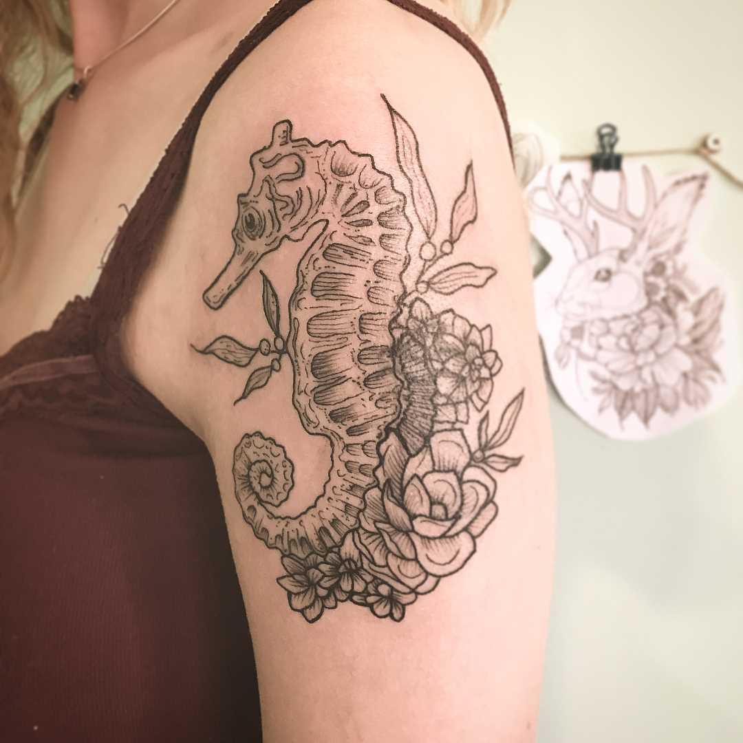 Tattoo do cavalo-marinho com flores no ombro da menina