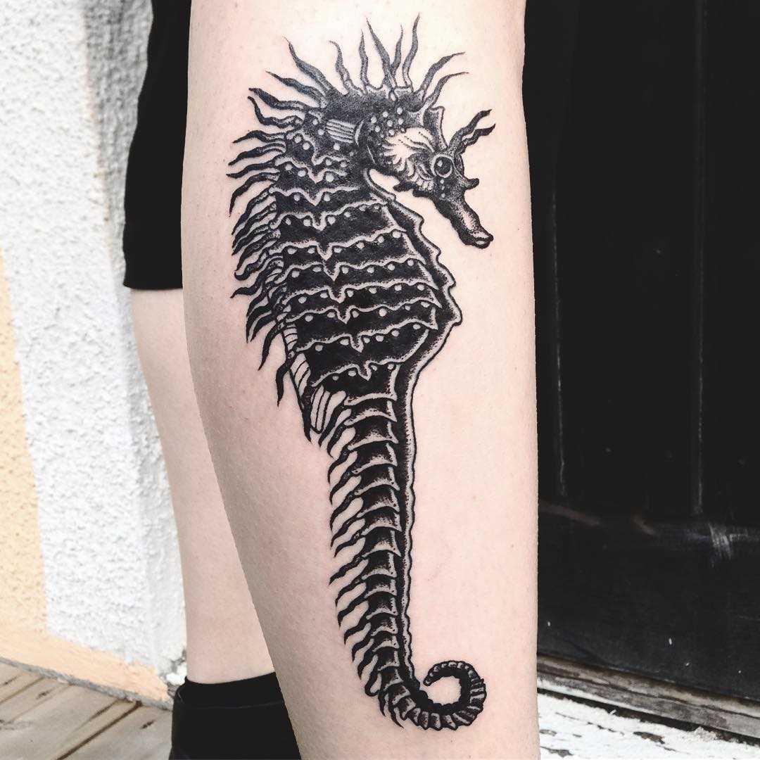 Tattoo do cavalo-marinho sobre a perna da mulher