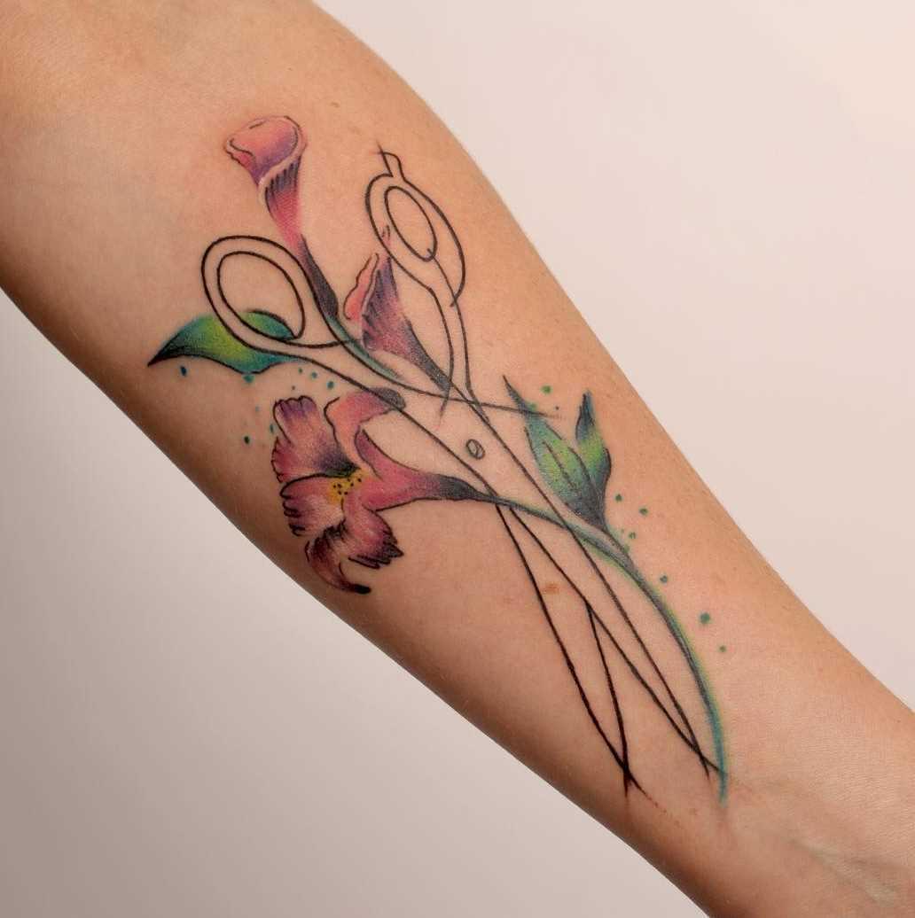 Tatuagem da tesoura com flores no antebraço da mulher