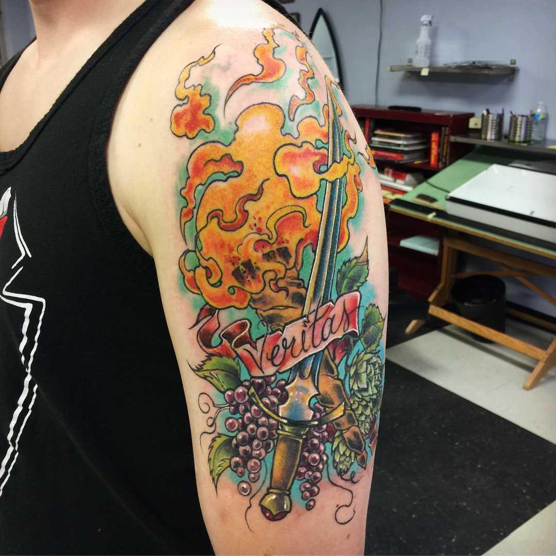 Tatuagem da tocha com a espada no ombro do cara