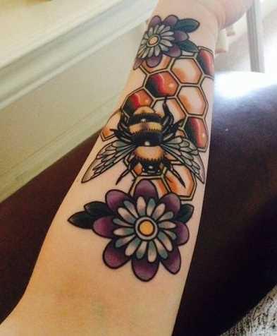 Tatuagem de abelha com flores no antebraço da mulher