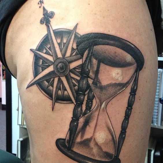 Tatuagem de ampulheta com o compasso sobre a perna de homens