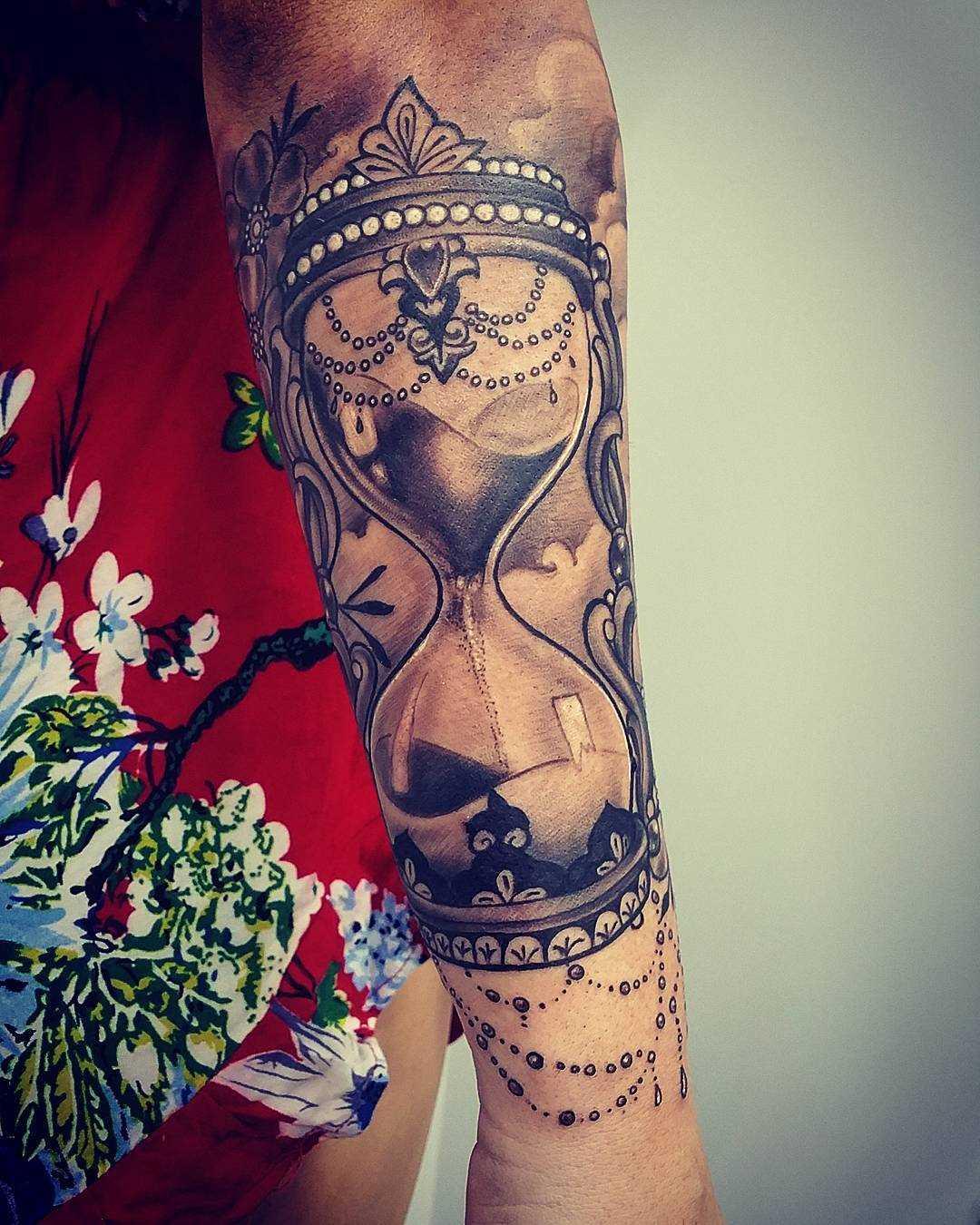 Tatuagem de ampulheta no antebraço da mulher