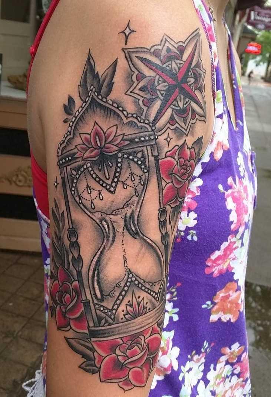 Tatuagem de ampulheta no ombro da mulher