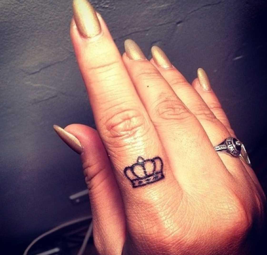 Tatuagem de coroa em seu dedo indicador, as meninas