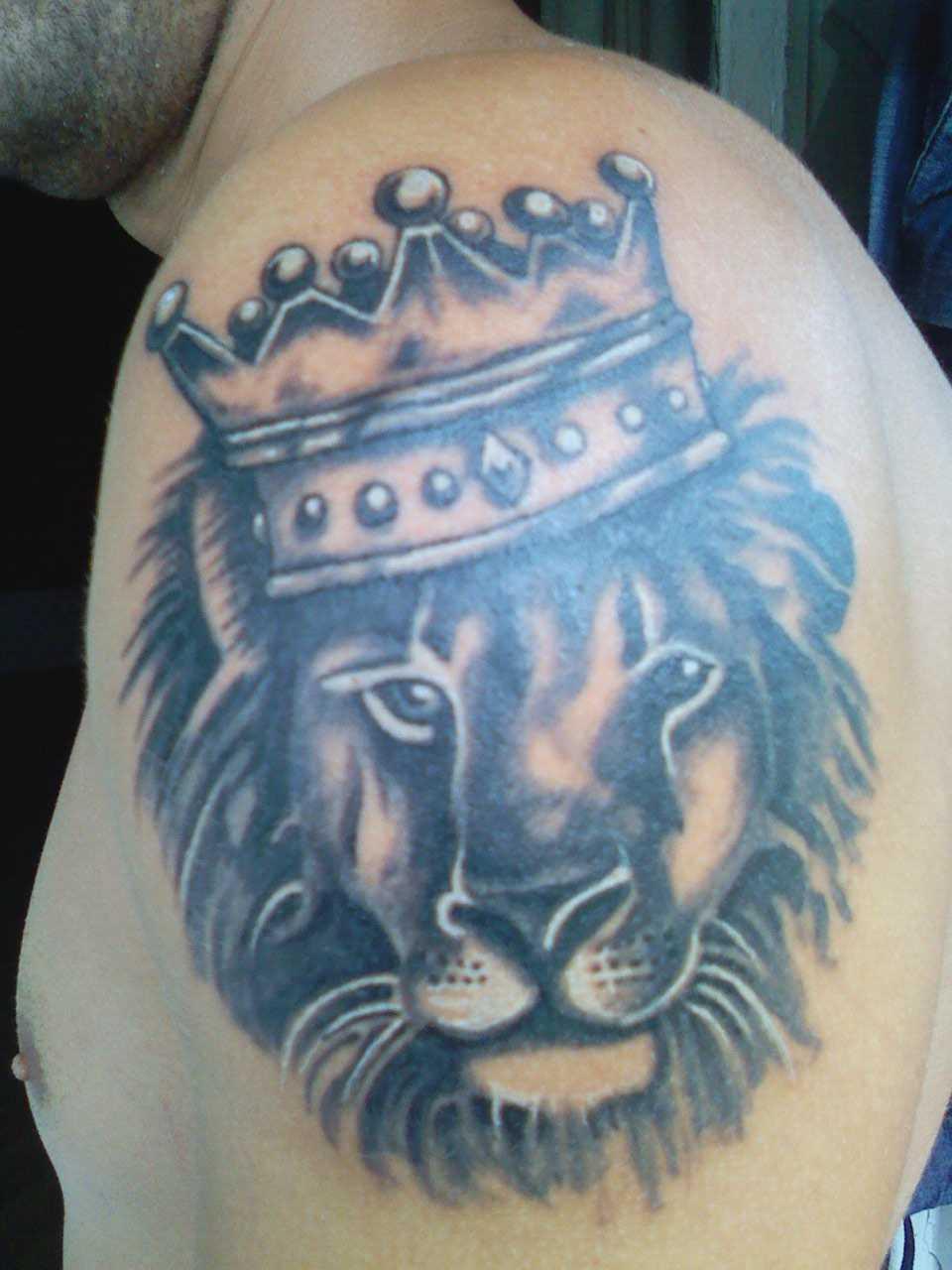 Tatuagem de coroa na cabeça de um leão no ombro de homens
