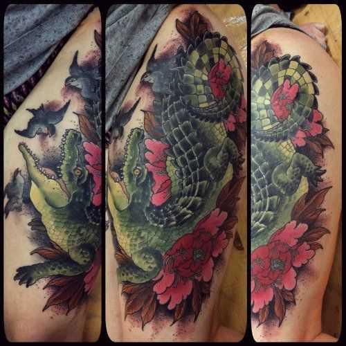 Tatuagem de crocodilo com flores no quadril da menina