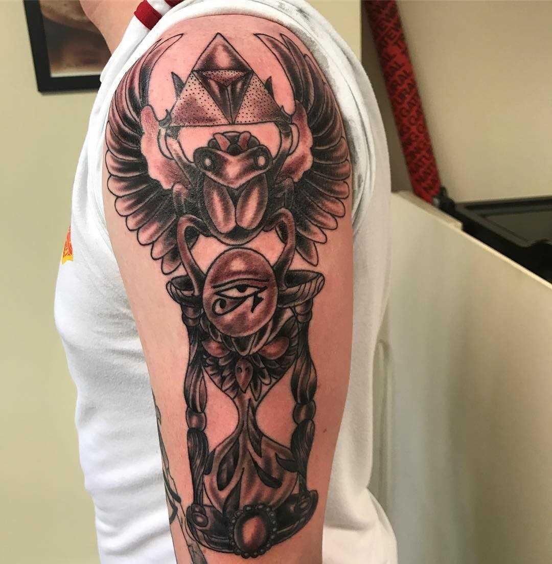 Tatuagem de escaravelho com uma ampulheta no ombro de homens