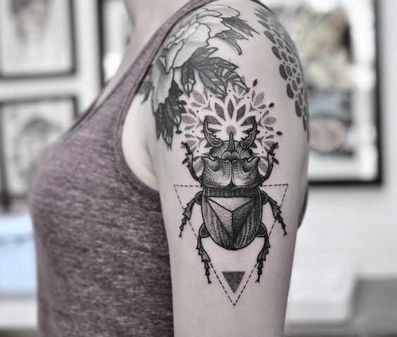 Tatuagem de escaravelho no ombro da mulher