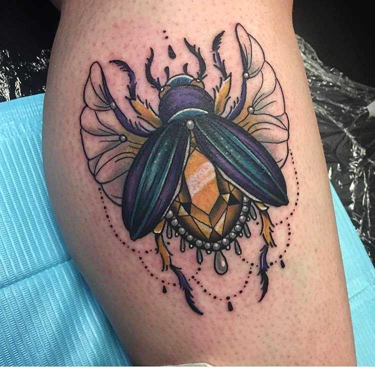 Tatuagem de escaravelho sobre a perna da mulher