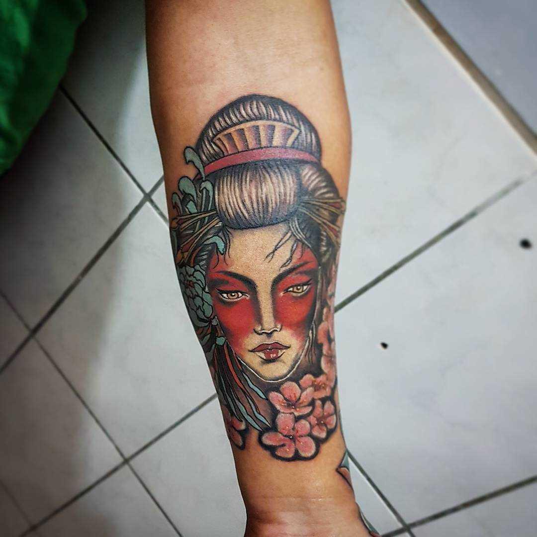 Tatuagem de gueixa com flores no antebraço da menina