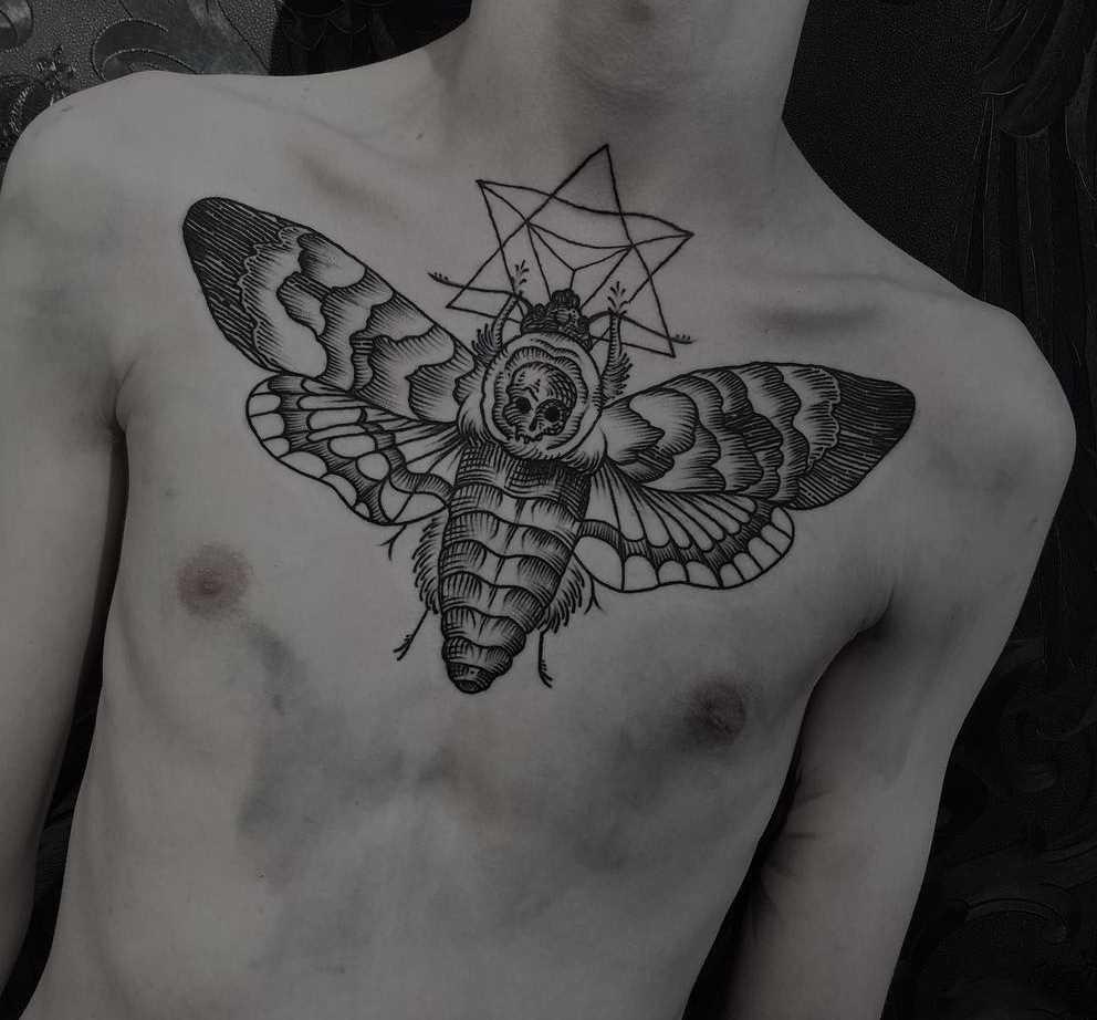 Tatuagem de inseto na cara no peito