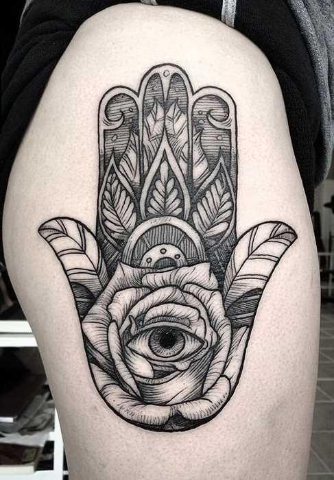 Tatuagem de joss hamsa no quadril da mulher